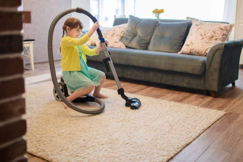 kid girl having fun while cleaning room with vacuum cleaner