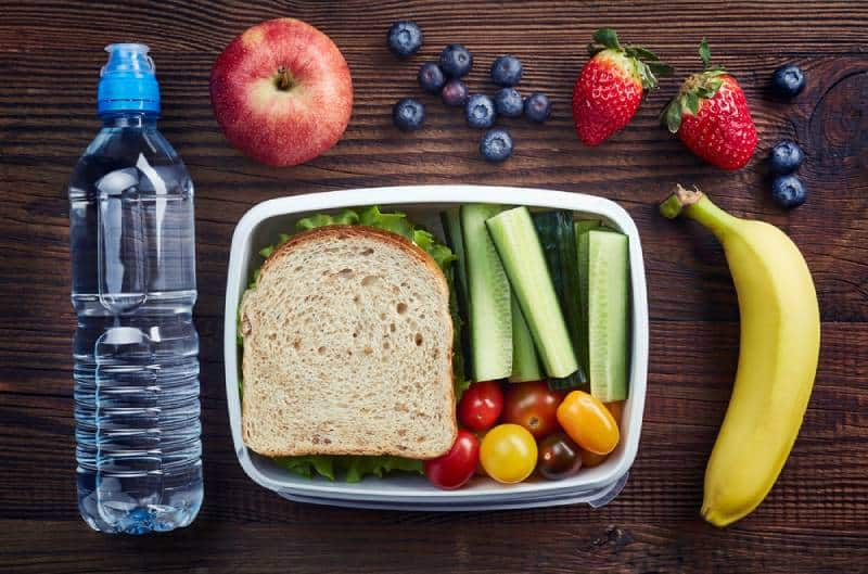Healthy lunch box with sandwich and fresh vegetables, bottle of water and fruits on wooden background