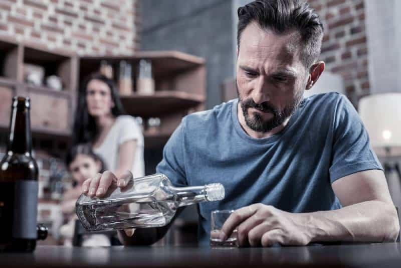 Serious unhappy sad man sitting at the table and pouring vodka into his glass while his wife and daughter watch