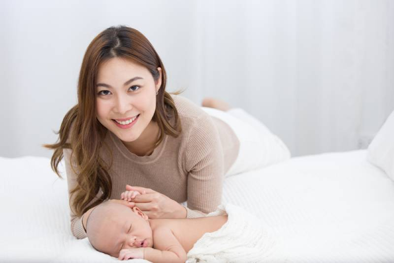 Mom holding her baby while being on bed