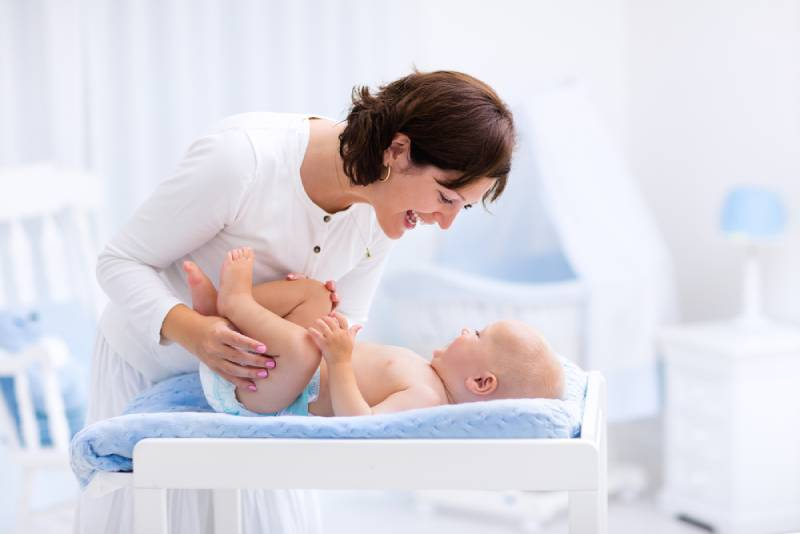 mother taking care of little boy in white sunny nursery with changing table, baby crib and rocking chair