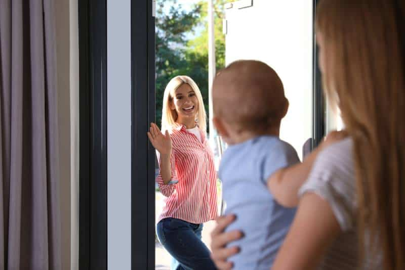 Mom leaving baby with a nanny at home and going outside