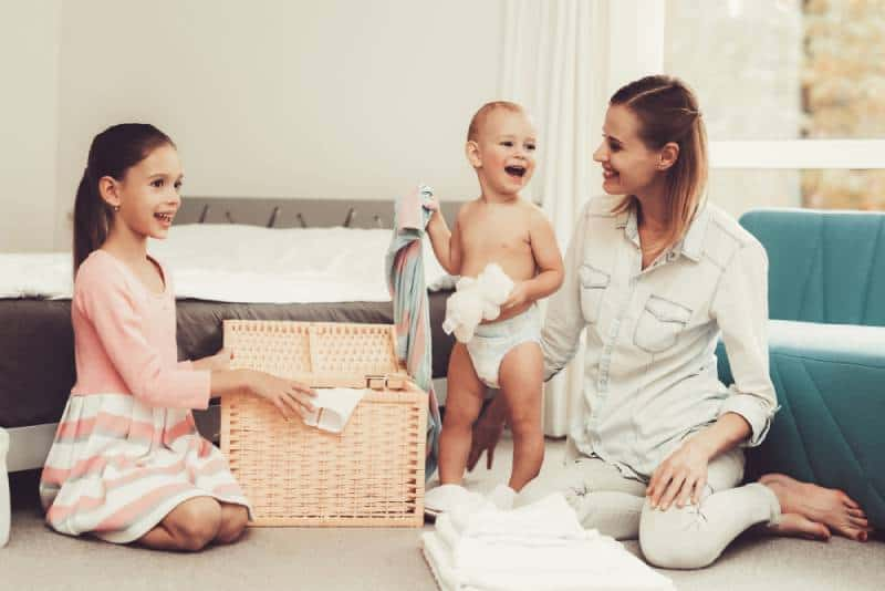 Girl helps her mom with taking care of a baby and house chores