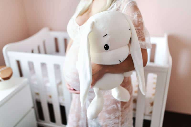 Close up of pregnant woman holding white bunny toy while standing in baby room