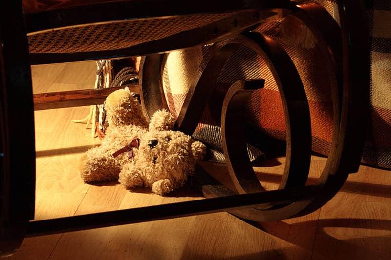 teddy bear lost under rocking chair
