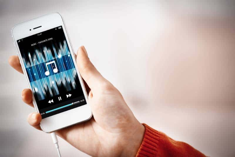 Music smartphone in female hand, on home interior background