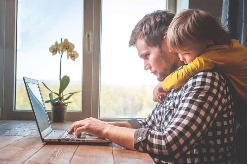 Dad working on his PC while his son sadly hugs him because he wants to play