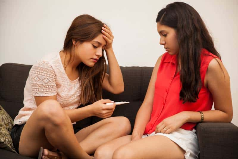 Sad and scared teen holding a pregnancy test and giving the news to her best friend while sitting on sofa indoors