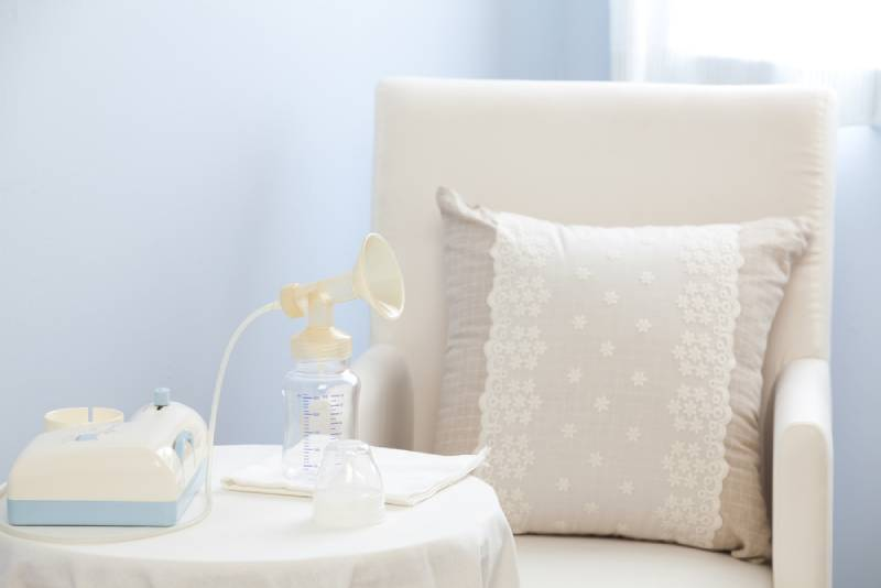 breast pump on a table next to a rocking chair in nursery