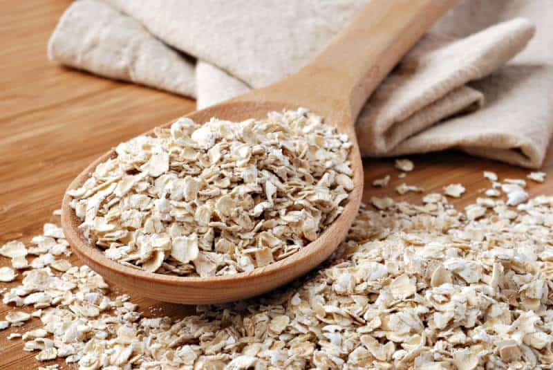 Whole grain oats with wooden spoon and homespun napkin