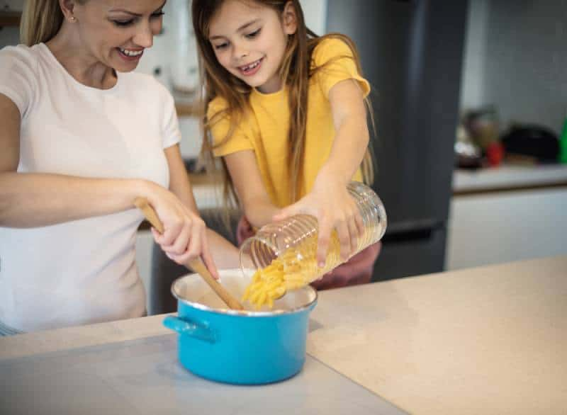 Happy mother and daughter preparing pasta in their kitchen