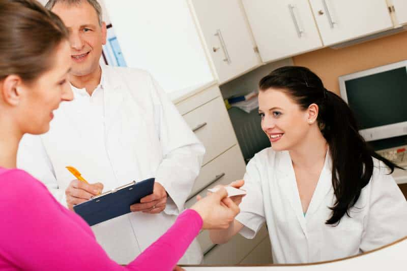 Patient in reception area of office of doctor or dentist, handing her health insurance card over the counter to the nurse, while doctor is there