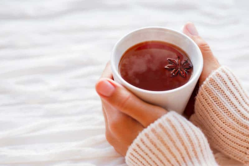 Women holds a cup of hot tea with anise star at home