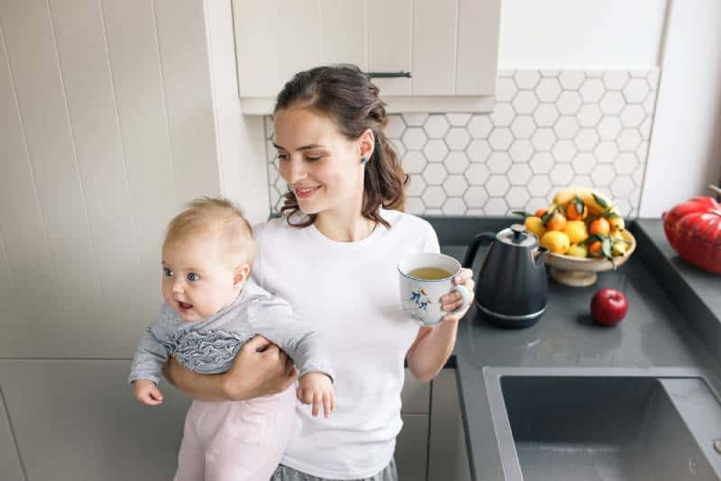 Mother in white drinking tea with baby in her hands in kitchen