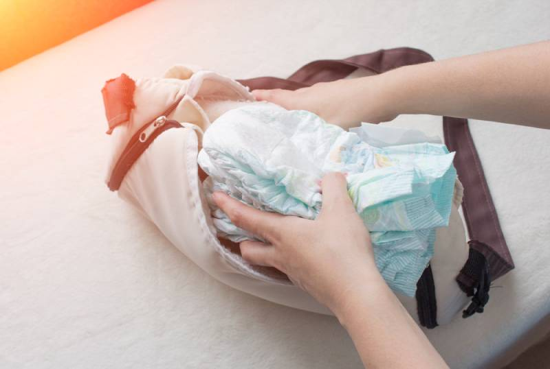 Female hands lay baby diapers in a bag on bed
