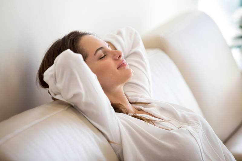 Calm millennial woman in white relaxing on soft comfortable sofa meditating or having daytime nap