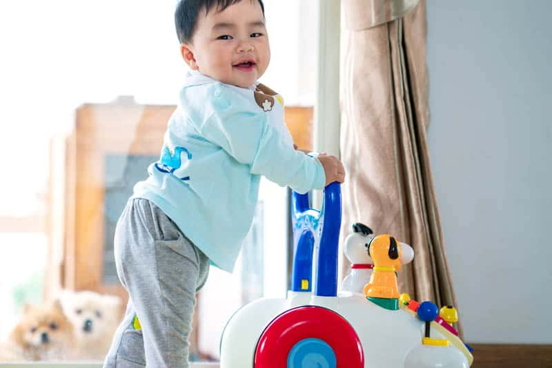 cute asian baby standing by activity table on wheels