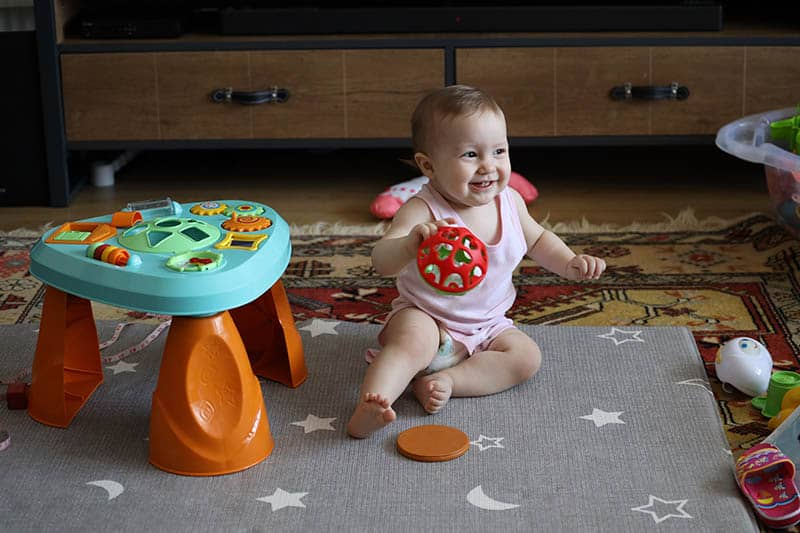 baby girl playing with baby activity table