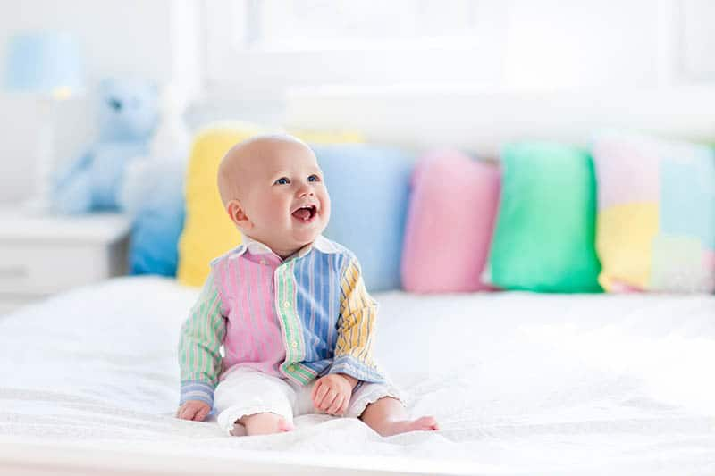 baby toddler sitting on bed with pillows colored pillowcases in background