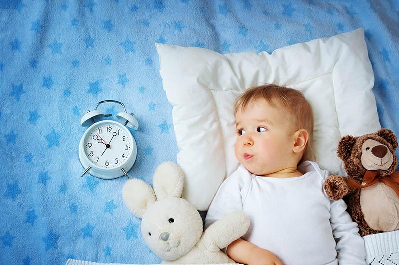 baby boy going to sleep on white pillow