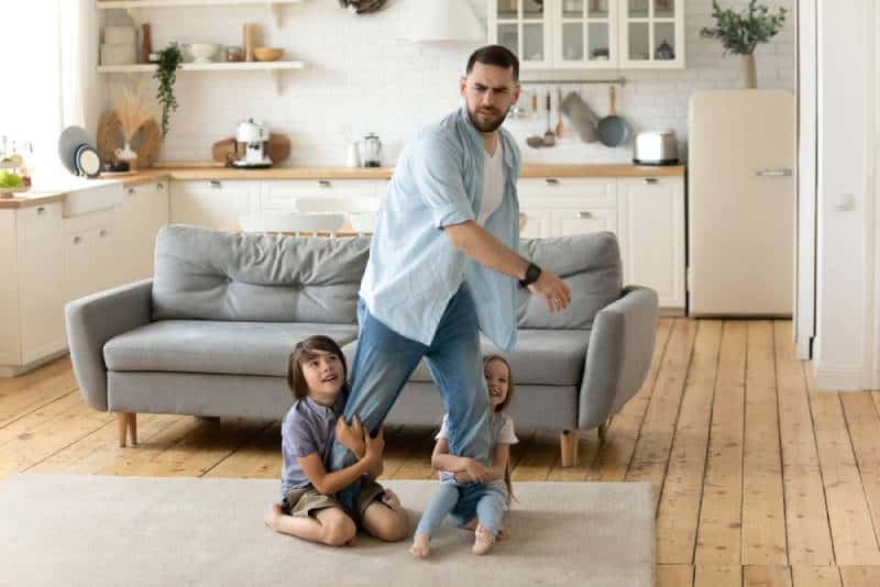 Hyperactive kids holding tired upset father legs and he doesn't want to play with them in the living room