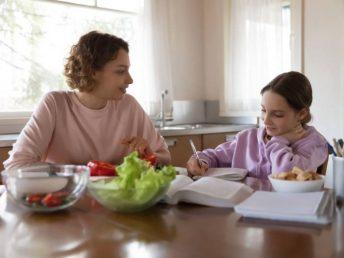 mum preparing vegetable salad helping tween school girl child doing homework sitting at kitchen table