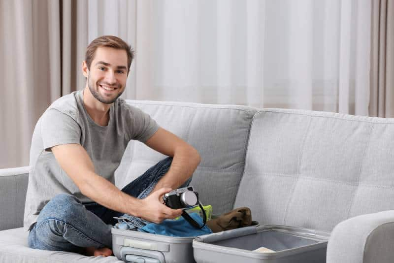 Man in grey shirt and denim sitting on a sofa and packing his suitcase
