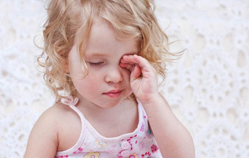 baby girl rubbing eyes tired