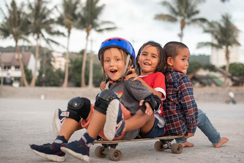 three kids on a skateboard