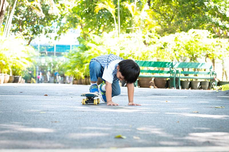 Toddler learning to ride a skateboard