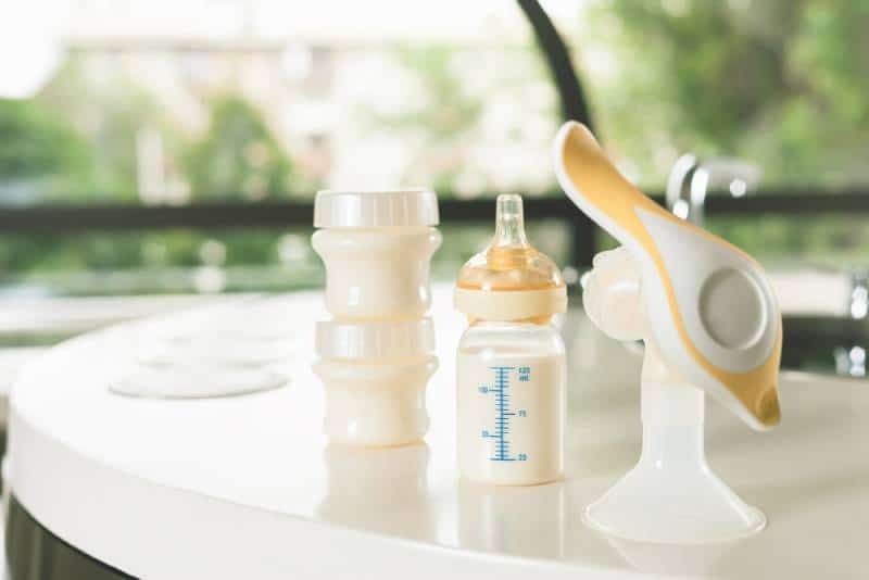 manual breast pump with a bottle of milk on table outdoors