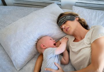 woman sleeping with crying baby