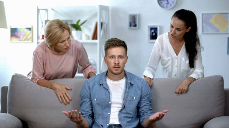 Male listening wife and mother criticism while sitting on sofa at home