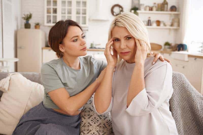 woman comforting middle aged upset mother, worrying about her health