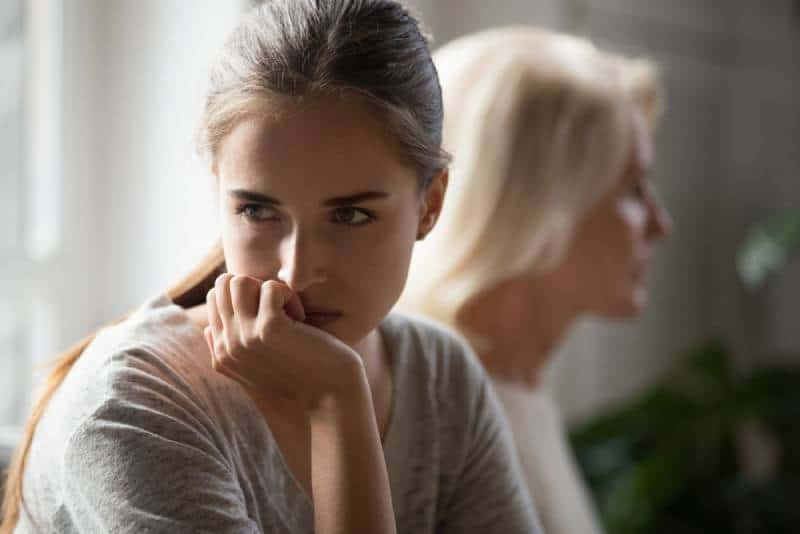 daughter and senior mother sit aside back to back avoid talking after fight at home