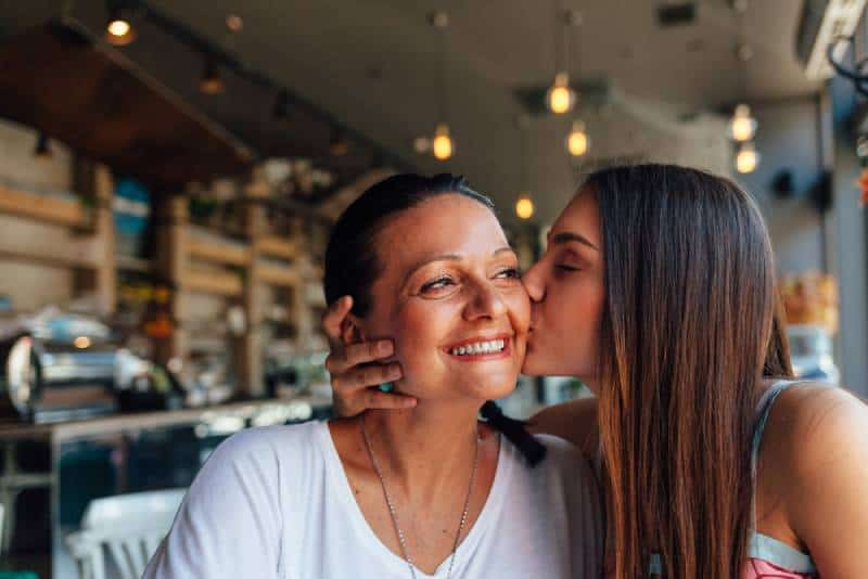 Happy daughter and mom in a nice cafe with copy space on blurred background