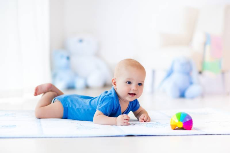 baby boy learning to crawl and playing with colorful rainbow ball toy in bedroom