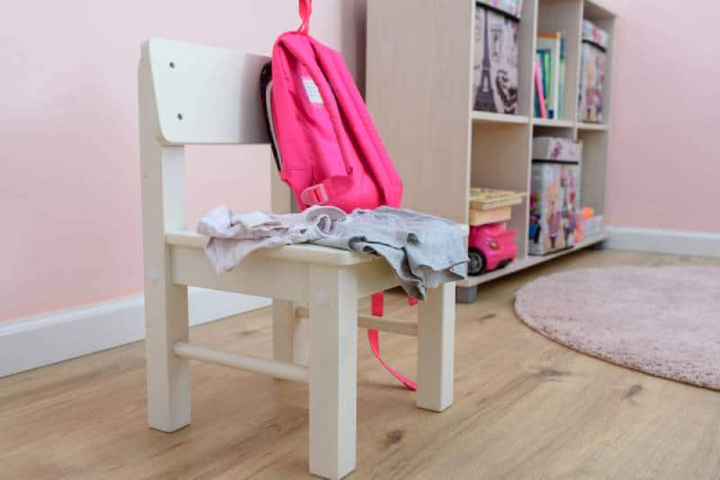 bag and clothes in children girl room on white wood chair