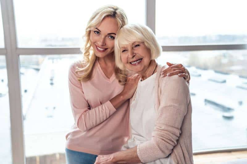 woman and her attractive daughter spending time together and hugging at home