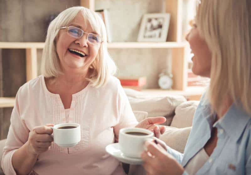 mother and her adult daughter are drinking coffee, talking and smiling while sitting on couch at home