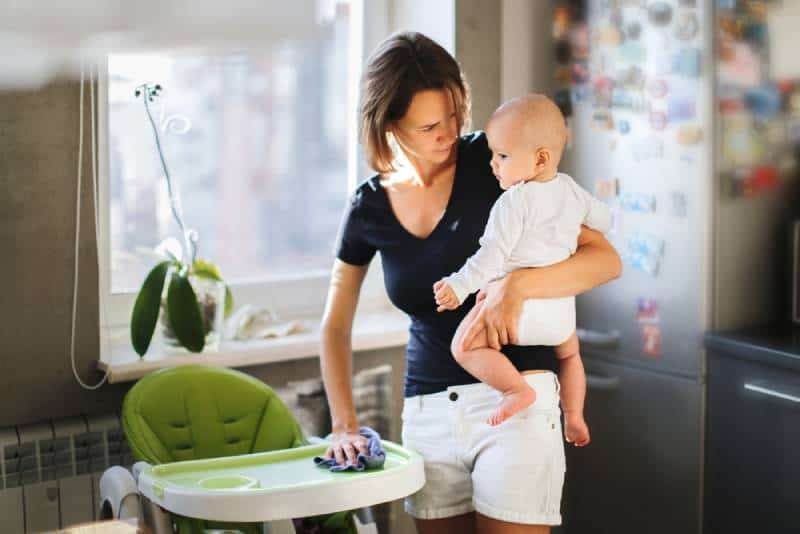 Mom with a baby in her arms wipes a highchair at home