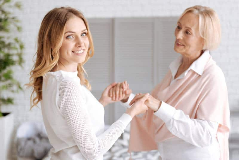 Mom holding her daughter's hands while smiling indoors