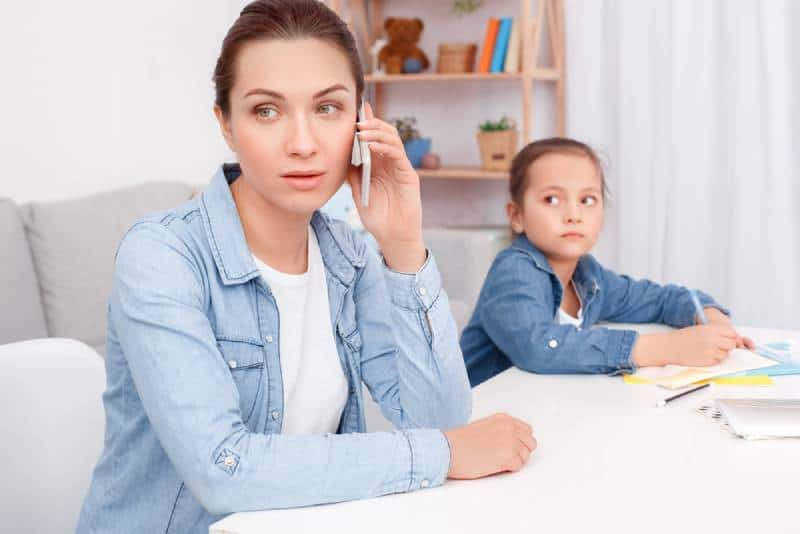 mom sitting at table talking on phone and not paying attention to her child