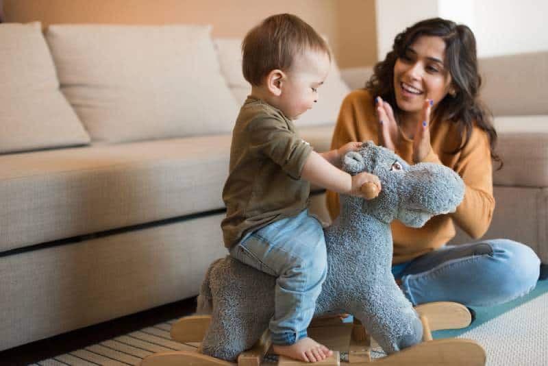 Baby boy playing with a rocking horse with mom's help indoors