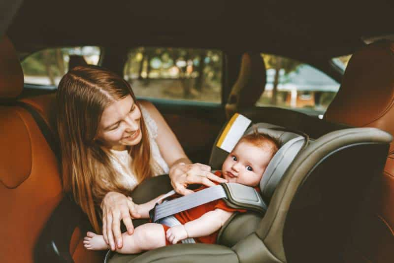 happy mom talking to a baby in a car seat