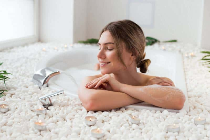 Woman lying in the hot bath with bubbles and having a great spare time
