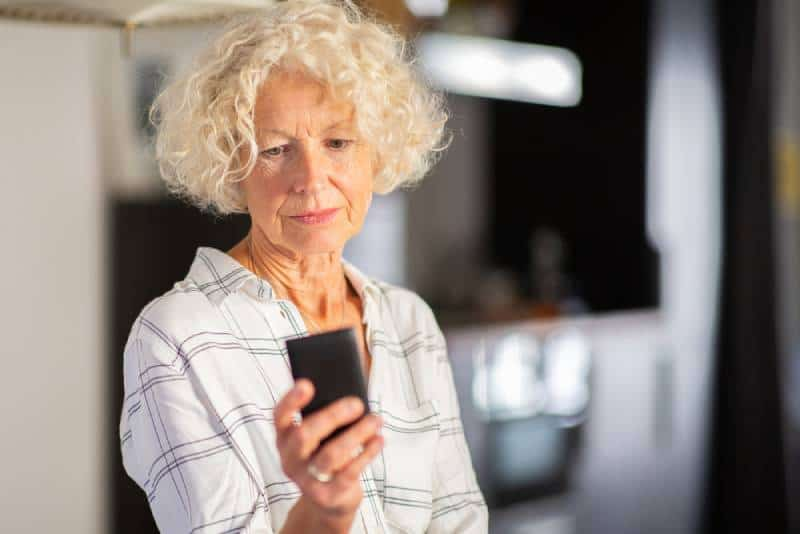 Close up portrait older woman looking at mobile phone screen