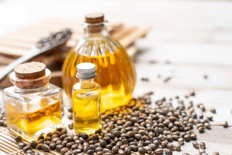 Castor oil in bottles on wooden background