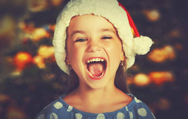 happy girl laughing at chistmas joke for kids