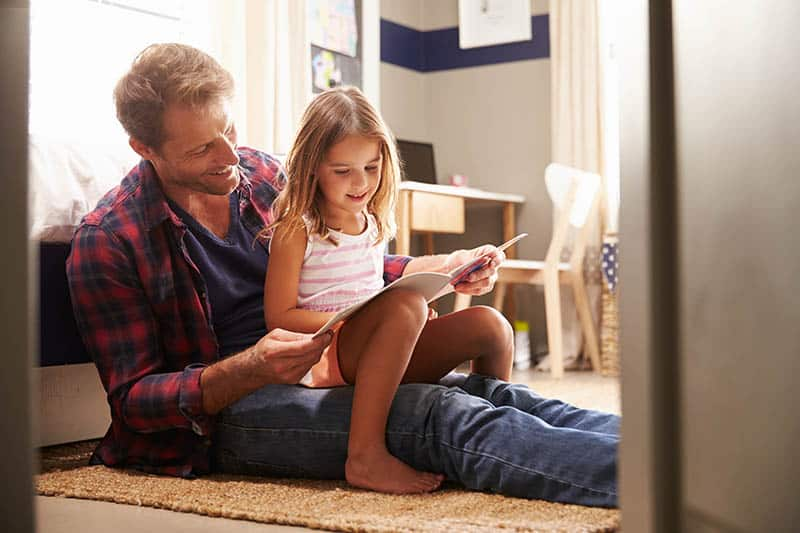 father and daughter sitting on floor reading a book